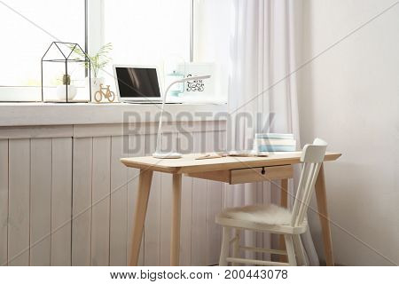 Modern comfortable workplace with laptop on window sill at home