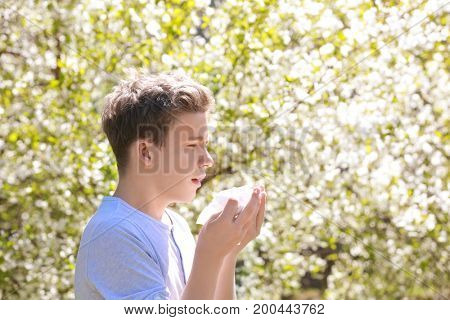 Allergy concept. Sneezing young boy with nose wiper among blooming trees in park