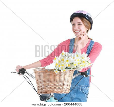 Young smiling girl with bicycle and basket of flowers on white background
