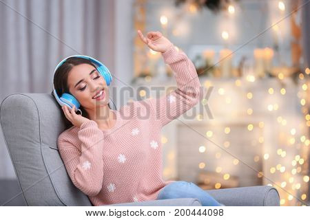 Beautiful young woman listening to music in living room decorated for Christmas