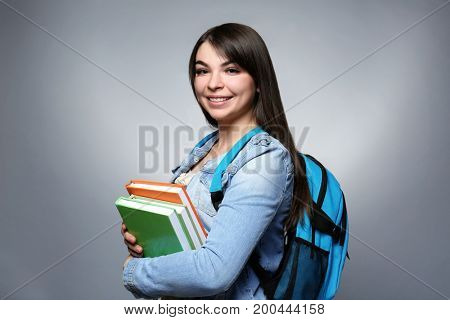 Young smiling girl with knapsack and books on grey background