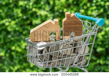 miniature wooden house in mini shopping cart with full of coins as real estate shopping concept.