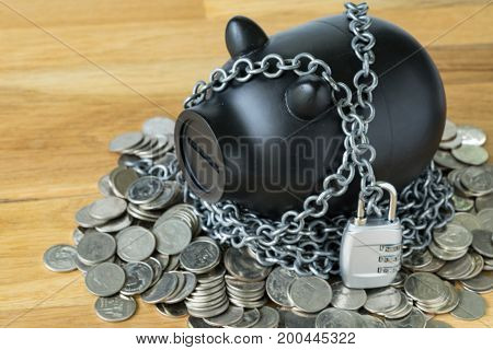 selective focus on black piggy bank with chains and lock pad and coins as security protection or financial saving concept.