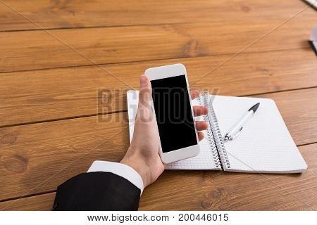 Male using mobile phone at workplace. Businessman working with portable computer, copy space on display, close up
