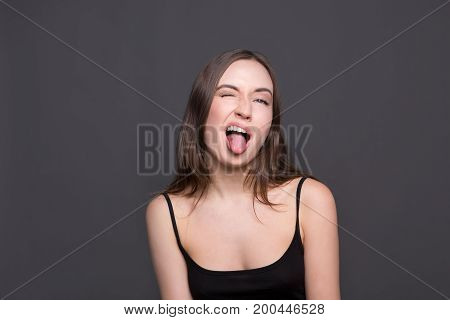 Beautiful modern girl shows tongue. Positive woman having fun and grimacing at camera, dark background