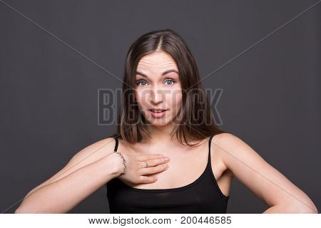 Surprised woman with arm on her body in disbelief. Girl looking in camera, dark background. Omg, wtf, human emotions concept