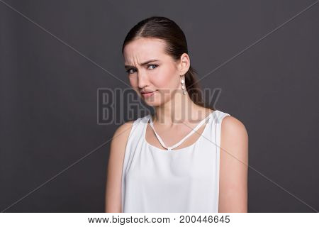 Puzzled attractive girl portrait. Shocked and surprised young woman looking at camera, dark background