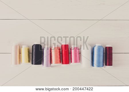 Colorful thread spools on wooden table flat lay background. Sewing string spools, copy space for text. Art, handicraft concept