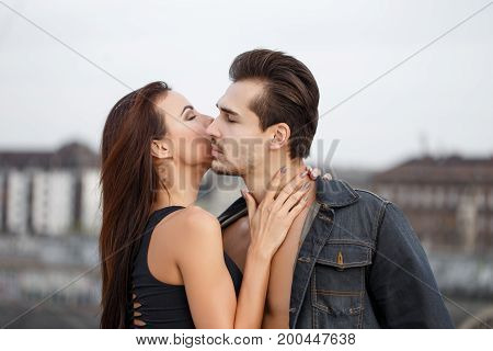 Young woman whispering secret love to sexy man outdoor