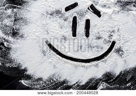 Smiley on white wheat flour at abstract black background. Top view on blackboard or table. Cooking dough or pastry.