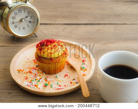 Yellow cupcakes put on a spherical wooden plate. Beside of cupcake have Vintage alarm clock and white coffee mug.All of it rests on wooden table.