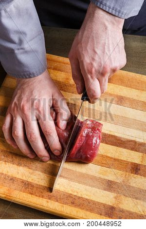 Man slicing filet mignon on wooden board at restaurant kitchen. Chef preparing fresh meat for cooking. Modern cuisine backgroung with copy space, vertical