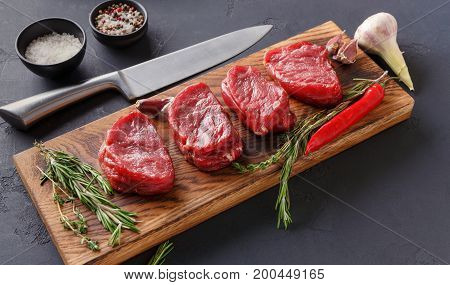 Raw filet mignon steaks with herbs and spices. Modern restaurant cuisine still life with fresh beef, salt, rosemary, garlic, chilli and chef knife on wooden board at black background, copy space