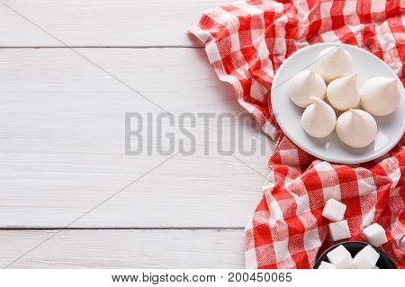 Sweet background. French meringues and lump sugar on white and red tablecloth on white wood with copy space