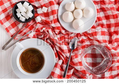 Coffee time background. Treats and cup of coffee on white and red checkered cloth. Glass of water, lump sugar and meringues on white wood, top view