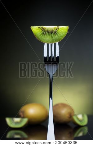 Sliced fresh and juicy green kiwi on the fork with whole kiwi in background healthy food and fruit salad concept