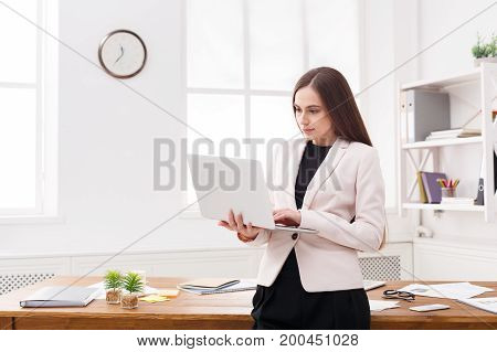 Young business woman standing and holding laptop at office