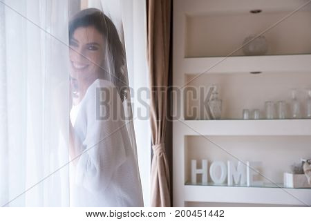A beautiful young woman standing in the window behind the curtain and smiling