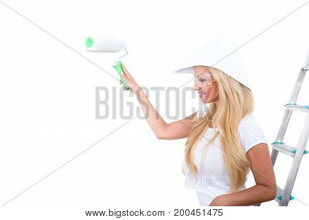 A beautiful young blond woman painting a white wall