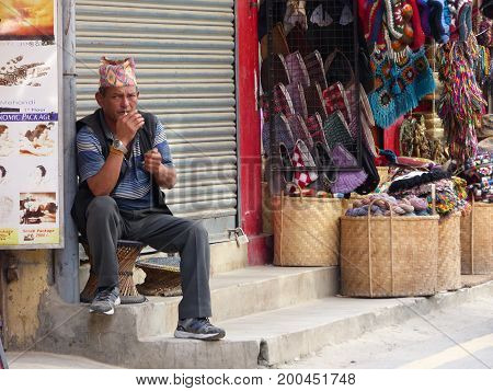Kathmandu, Nepal, september 4, 2015: Rush in streets of Thamel, the tourist place in Kathmandu, Nepalese trader smoke while waiting for customers