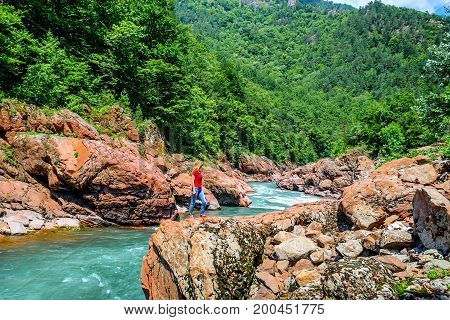 Back view of beautiful young woman hiker walking on scenic background with summer mountain river