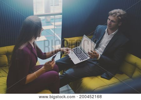 Handsome businessman in formal suit is showing graphs on screen of laptop to his female caucasian colleague while both sitting on sofas in office area for work meetings