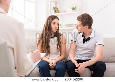 Young couple arguing on couch during therapy session. Relationship problems, family issues concept