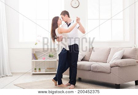 Young couple dancing at home, copy space. Romantic rest, man and woman having fun