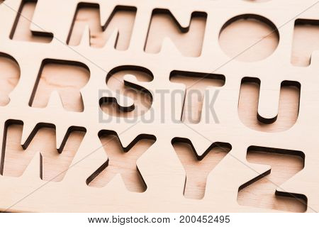 English alphabet stencil closeup, empty sorter for kids development