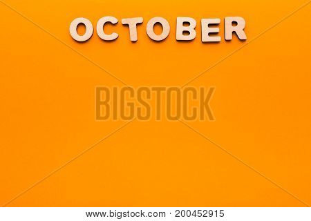 Word October made of wooden letters on orange background. Month planning, timetable concept