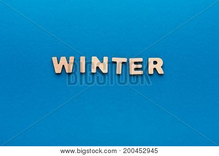 Word Winter made of wooden letters on blue background.Month planning, timetable concept