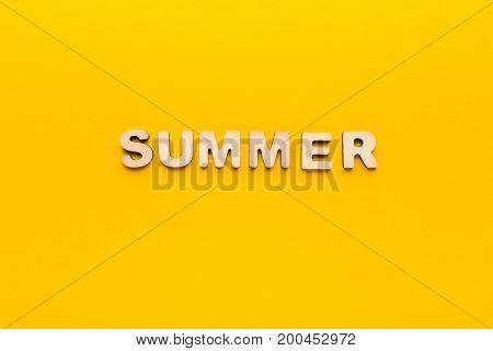 Word Summer made of wooden letters on yellow background. Month planning, timetable concept