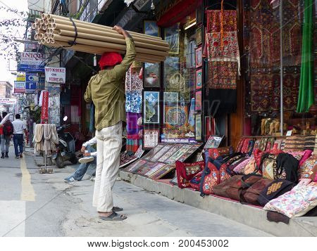 Kathmandu, Nepal, september 4, 2015: Rush in streets of Thamel, the tourist place in Kathmandu, Man with tubes on the head