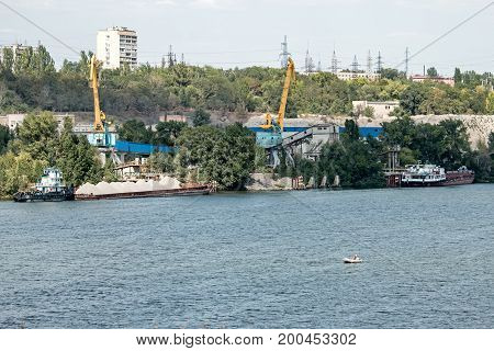 Cargo river port in Zaporozhye cranes load barges.