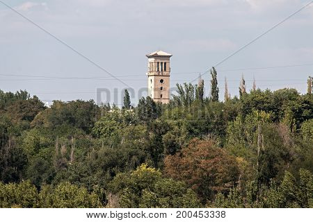 Abandoned lookout tower on a background of blue sky and lush forest