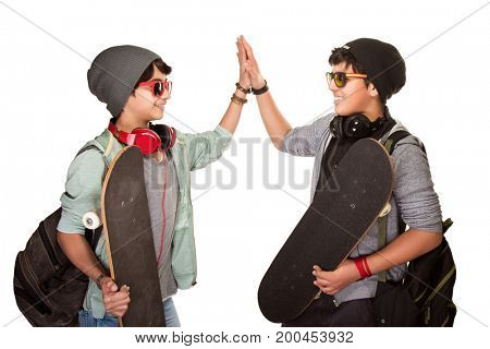 Two happy skateboarders acclaiming each other isolated on white background, best friends wearing stylish hats, sunglasses and listening music from earphone, modern life of a young people
