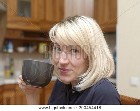 Young blonde woman having tea or coffee a modern kitchen interior in the background