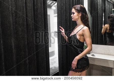 Young Brunette Woman Looking out of room window