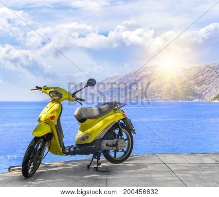 Yellow brand-less moped on the beach on a summer day.