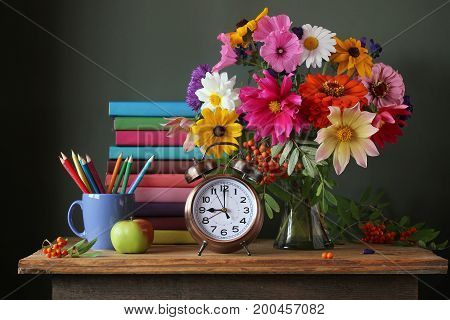 Back to school. September 1 knowledge day. The teacher's day. Still life with autumn bouquet and school supplies. Textbooks.