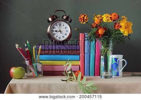 Back to school. September 1 knowledge day. The teacher's day. Textbooks and bouquet alarm clock Apple and colored pencils on the table. Still life.