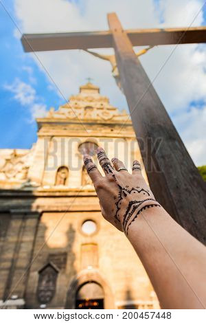 Conceptual photo of Bernardine Church in Lviv and female hand stretching to the skies. Religious themes. The concept of human attraction to faith. The idea of finding humanity of the Lord God.