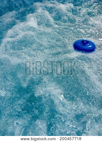 Blue dispenser for chlorine tablets in the swimming pool