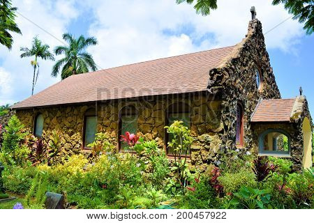 Historic Christ Memorial Episcopal Church built during the early 1900s with stone lava rocks surrounded by a cemetery and lush gardens taken at Kilauea in Kauai, HI