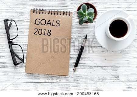 Words Goals for 2018 writting in notebook near glasses and cup of coffee on grey wooden background top view mockup.