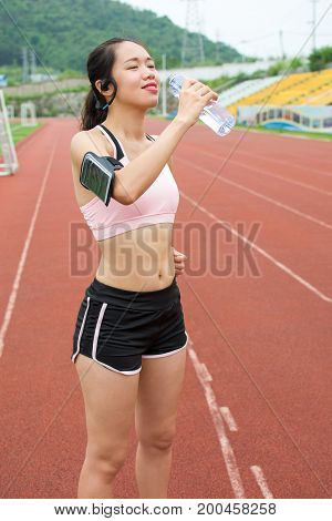 Female Jogger Hydrating On A Running Track