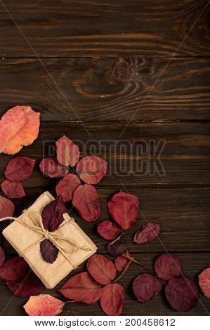Flat lay frame of autumn crimson leaves and gift boxes on a dark wooden background. Top view.