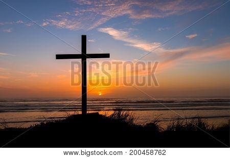 Black cross on a beach with a haze sky sunset behind it.