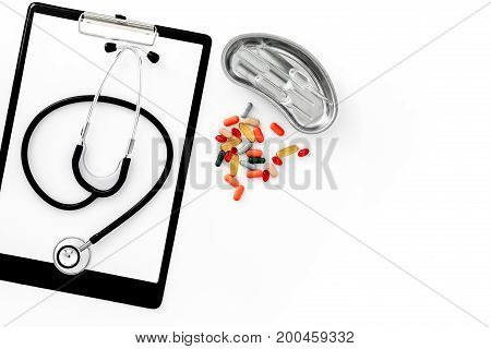 Doctor's table. Clipboard, stethoscope and cuvette with ampoulie on white background top view.