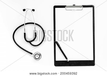 Doctor's accessories. Clip pad and stethoscope on white background top view.